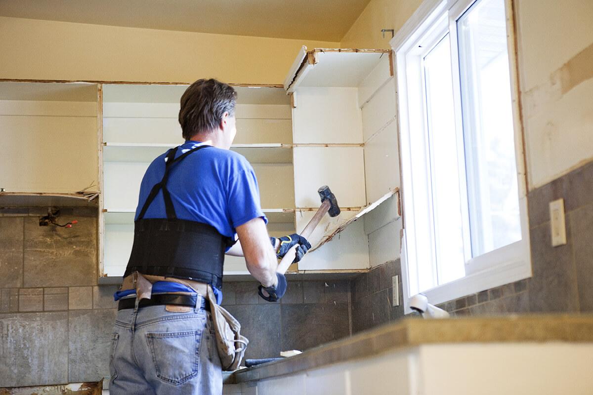 Homme tenant une masse détruit des armoires de cuisine